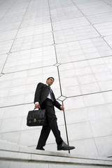 Businessman with briefcase walking down steps