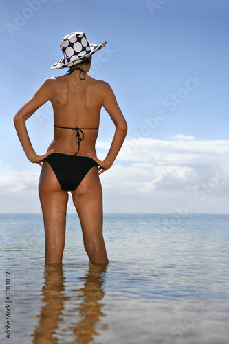 Brunette at the beach with her back to the camera