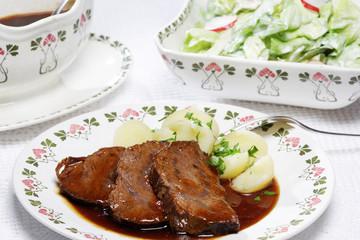Rinderbraten mit Kopfsalat und Salzkartoffeln.