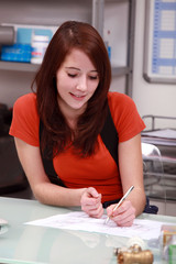 red-haired girl sitting at desk