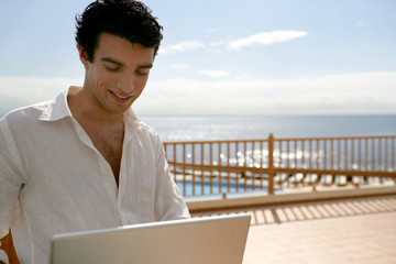 Man using a laptop on a terrace next to a pool