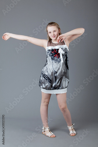 young happy girl.  little girl on a gray background.  Happy chil