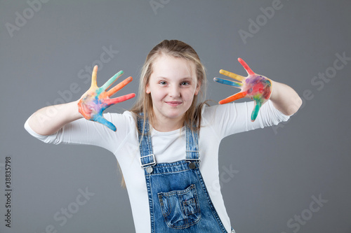 little girl on a gray background. hands in the paint.
