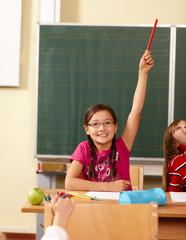 Mädchen meldet sich in Grundschule
