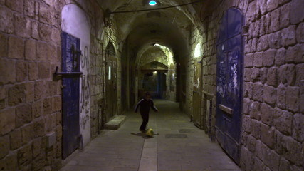 Stock Video Footage of a boy playing soccer in an ancient alley filmed in Israel at 4k with Red.