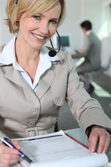 Woman smiling with headset and questionnaire.