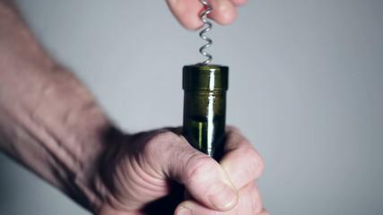 Man's hands open a wine bottle