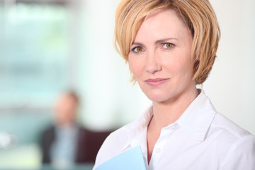 Woman stood in office with colleague in background