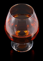 cognac in goblet isolated on black background