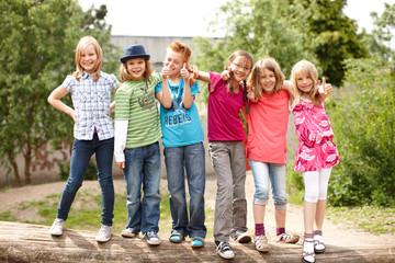 Gruppe fröhlicher Kinder auf Baumstamm