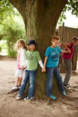 Kinder stellen sich um einen Baum