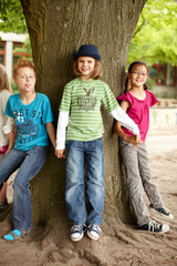 Gruppe Kinder stellen sich um einen Baum