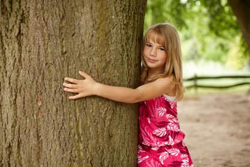 Mädchen umarmt Baum