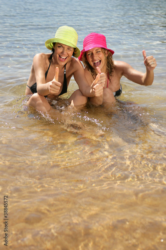 Two female friend at the beach giving the thumbs-up