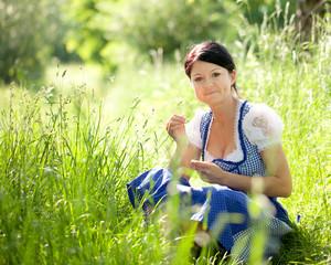 Frau sitzt in der grünen Wiese