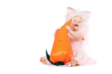 Happy baby girl plays with a carrot