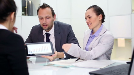 Consultants explaining something on digital tablet to client