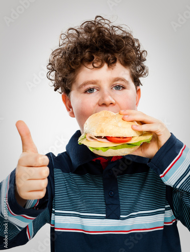 Boy eating big sandwich showing OK sign