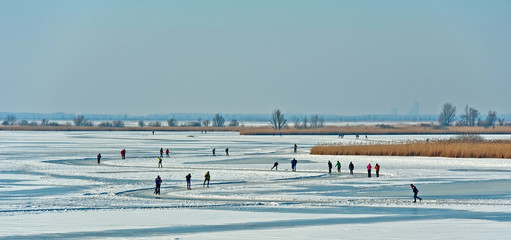 People skating on a frozen lake in winter