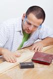 Man furbishing wooden planck poster