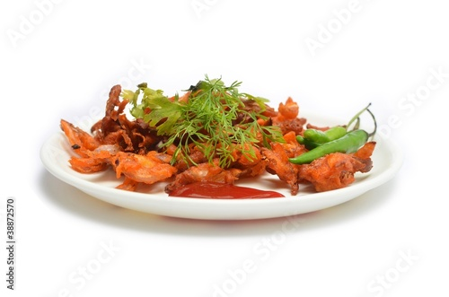 a plate of onion pakodas isolated on white background
