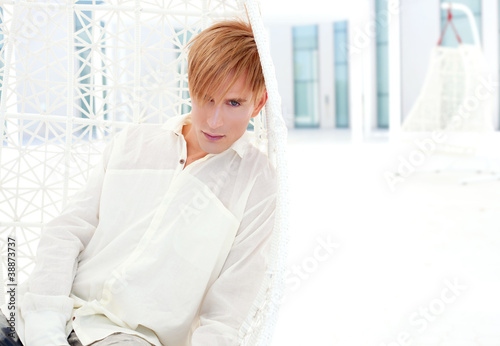 blond modern man portrait in summer terrace