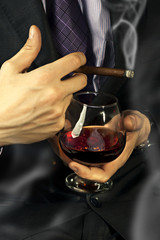 Old Brandy Glass at male hand, smoking cigar