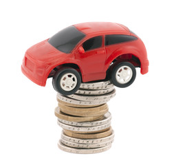 Red toy car on stack of euro coins