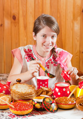 Girl in traditional  clothes eating pancake