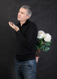 Man hiding a bouquet of flowers on gray background