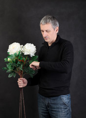 Man holding a bouquet of flowers on gray background