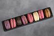 Macarons multicolores alignés, fond gris