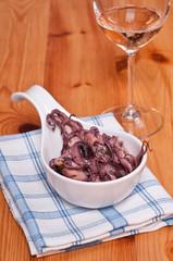Tintenfisch als Salat und Weinglas mit Rose