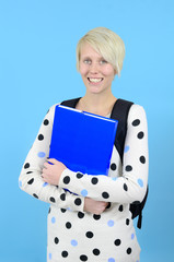 Cute female student on blue background