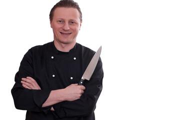 Mann in einer Kochjacke und einem Küchenmesser