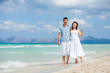 Happy young couple walking on beach