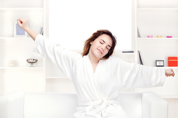 girl in bathrobe at home stretching arms