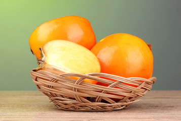 Appetizing persimmons in pad on wooden table on green background