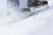 Snow flying from braking, ice skates blurred