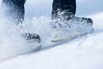 Two breaking ice skates with flying snow