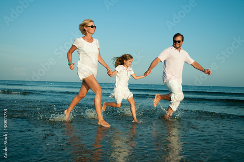 Happy summer vacation - family playing at the beach