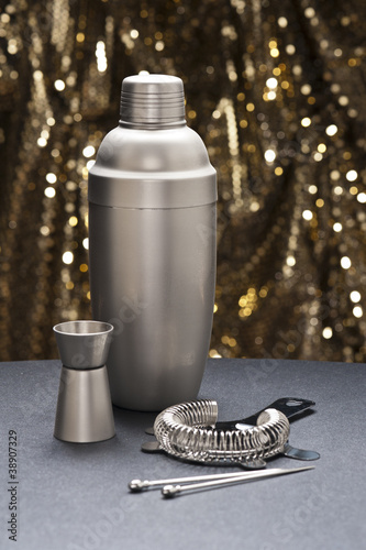 Bartender tools in front of a gold glitter background