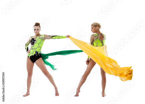 Two beauty gymnasts fight with flying fabric