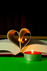 Open book with burning candle