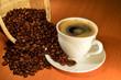 Постер, плакат: кофе с пенкой в белой чашке и рассыпанные из корзинки зёрна