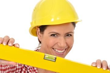 Handwerkerin mit Helm hält eine gelbe Wasserwaage in die Kamera