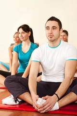 group of young people stretching in aerobics class