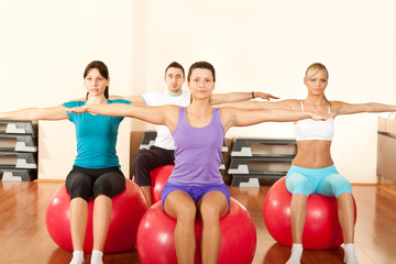 group of people doing  exercises on fitness ball