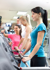women in gym with personal trainer