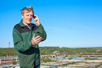 Mature man in working clothes speaking on cellphone outdoor